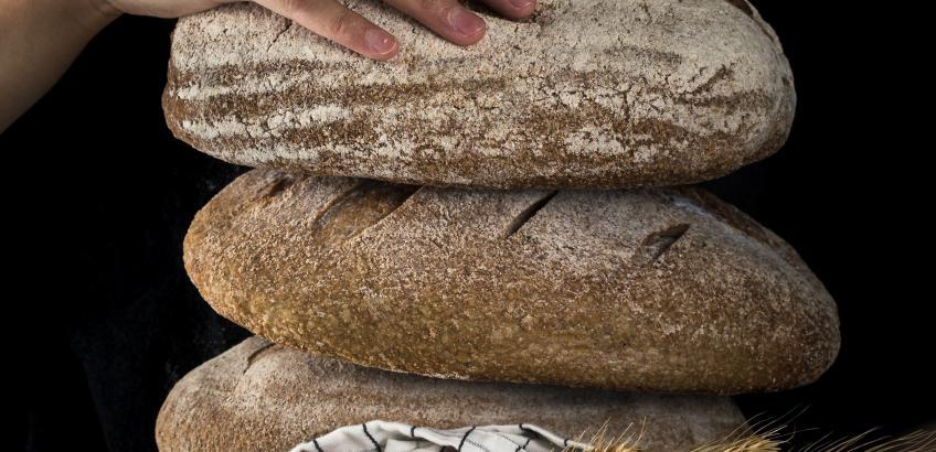 Et par hænder holder en stak brød